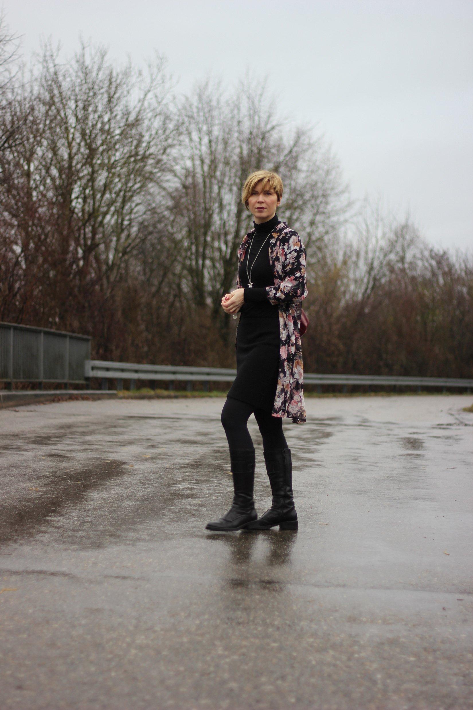 Conny auf regennasser Straße - ganz in Schwarz mit Longbluse im Blumenprint