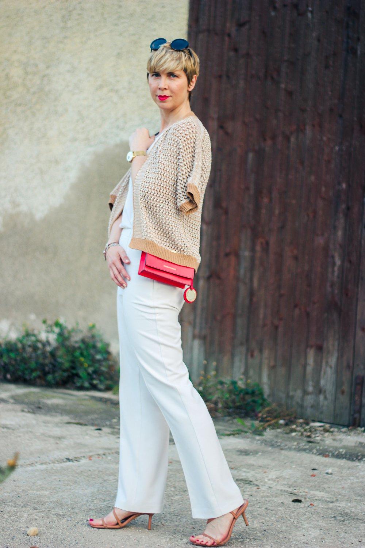conny doll lifestyle: Strickjacke, helle Hose, Sandalen, rote Tasche, kurze Haare